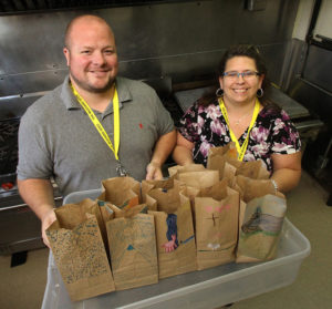The Mustard Seed's Director of Central Alberta Byron Bradley and Volunteer Resources Coordinator Cori Capner with lunches destined for a local school.