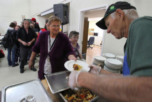 Ed Primas, a volunteer fro the Lutheran Church of the Good Shepherd, dishes out hot food.